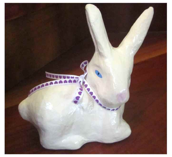Paint and ribbon have transformed this bunny into a cute Easter decoration.