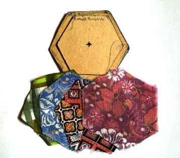 The original cardboard hexagon templates - one large for the material and one smaller for the temporary paper inserts.